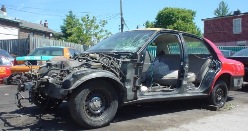 Beaten-up taxicab is missing hood and doors, but still has a trunk