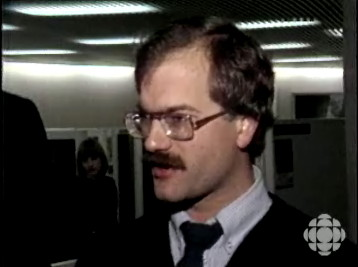 Old video still frame of Jack Layton with full head of dark-brown hair and full brown moustache