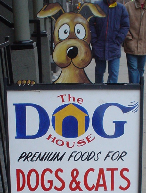 Handwritten sign reads The DOG HOUSE PREMIUM FOODS FOR DOGS & CATS and is topped by a dog's surprised-looking face