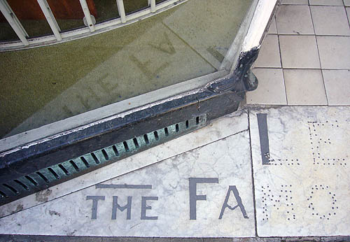Aging marble floor tiles before an angled store window read THE FAMOUS
