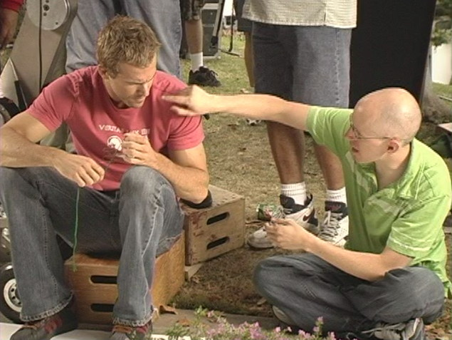 Bald, thin John August reaches over to tall, muscular Ryan Reynolds