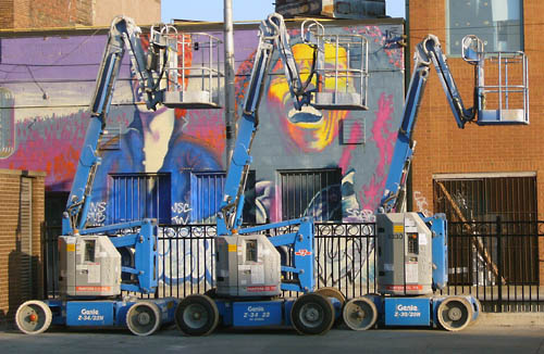Three blue cherrypickers parked nose to tail beside a fence and a wall graffitied with the picture of Bob Marley