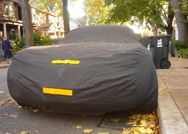 Tonneau cover with orange reflectors on front covers sports car as old lady walks by on opposite sidewalk