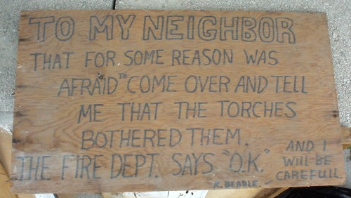 "Handmade sign reading ''To my neighbor that for some reason was afraid to come over and tell me that the torches bothered them. The fire dept. says ""O.K."" and I will be carefull.—K. Beadle"