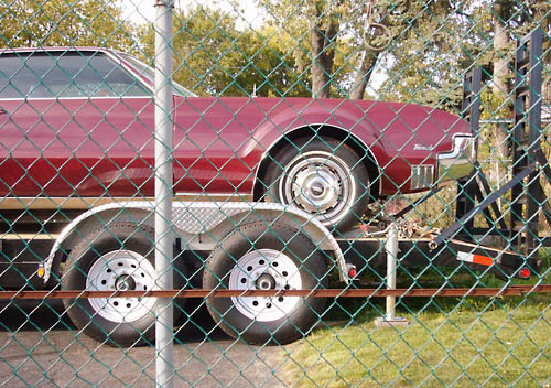 Seen through a fence, a burgundy Olds Toronado, with prominent round fender, sits on a trailer with two sets of wheels