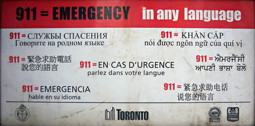 Placard reading 911 + EMERGENCY in any language with translations in seven languages