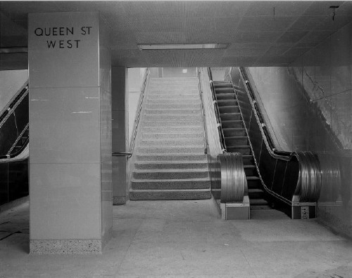 Spare subway-station concourse by escalators uses large glossy tiles and reads QUEEN ST WEST