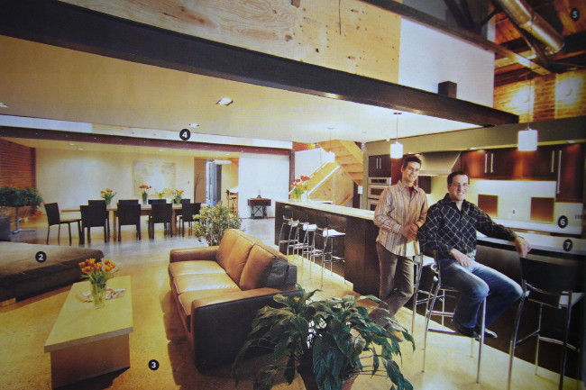 Two guys in shirts sit at ginat bar in vast loft space