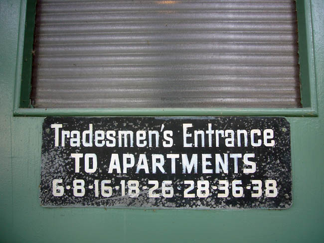 Handlettered sign reads Tradesmen's Entrance TO APARTMENTS 6·8·16·18·26·28·36·38