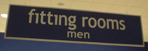 Sign reads 'fitting rooms men' in Trebuchet (with fi ligature)