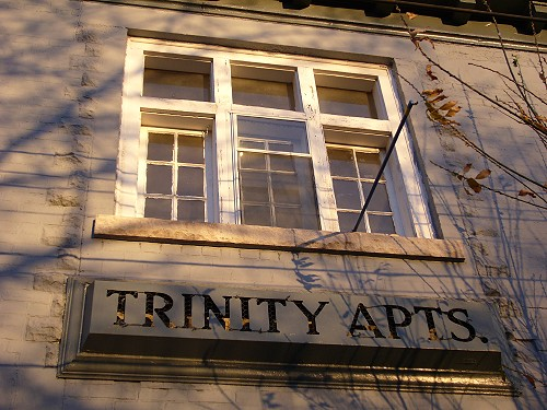 Sign below apartment window reads TRINITY APTS. in letters cut out from a protruding box