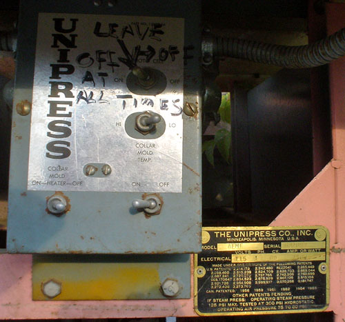 Metal control panel is labeled UNIPRESS and has LEAVE OFF AT ALL TIMES written in marker. Manufacturer's brass-coloured plate reads THE UNIPRESS CO., INC. MINNEAPOLIS, MINNESOTA USA and lists many patent numbers