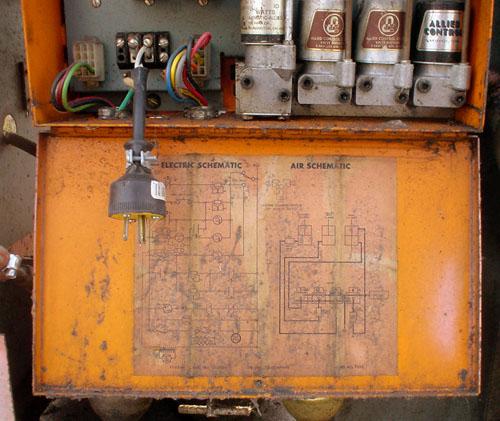 Orange-coloured metal hinged door has ELECTRIC SCHEMATIC and AIR SCHEMATIC diagrams on its inside. Inside the box above it sit a power plug and some cylinders