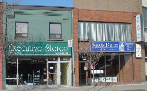 Adjacent storefronts – Executive Stereo and Salon Pride – have signs typeset in University Roman