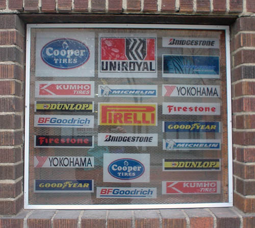 Recessed window has 21 decals with automotive logos, including COoper Tires, Uniroyal, Firestone, Pirelli, and Kumho (twice)