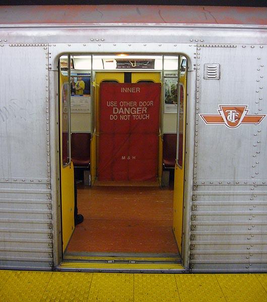 Banner covering a subway-car door opposite an open door reads INNER USE OTHER DOOR DANGER DO NOT TOUCH