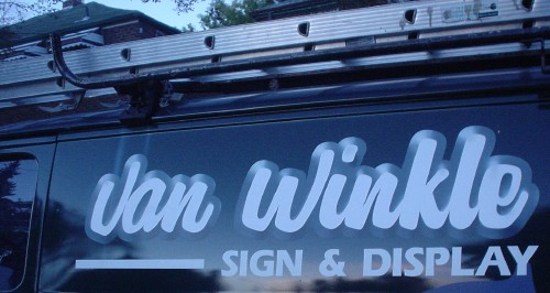 Deep-blue van has sky-blue airbrushed script letters reading Van Winkle (and SIGNAGE below in sky-blue Eras)