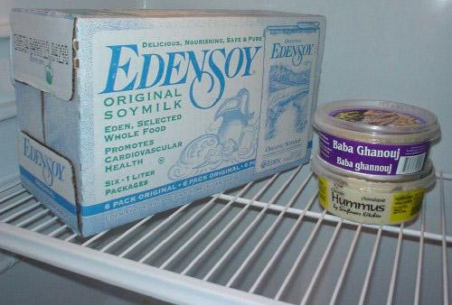 Top shelf of refrigerator holds case of Edensoy, baba gannouj, hummus