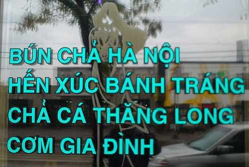Shop window has Vietnamese sign made of teal adhesive letters in Helvetica