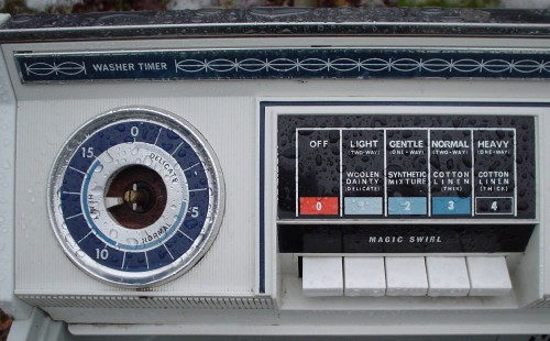 Rain-dappled used washing-machine has a missing knob and push-buttons with multicoloured legends reading 'Light (Two-Way) Woolen Dainty (Delicate)' and others