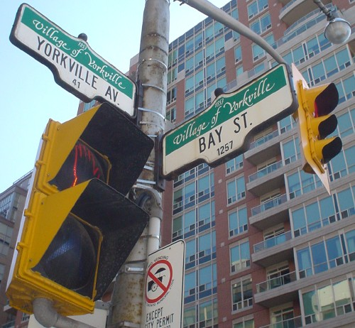 Street signs at the corner of Bay St. and Yorkville Av. have top banners reading Village of Yorkville in Le Griffe script