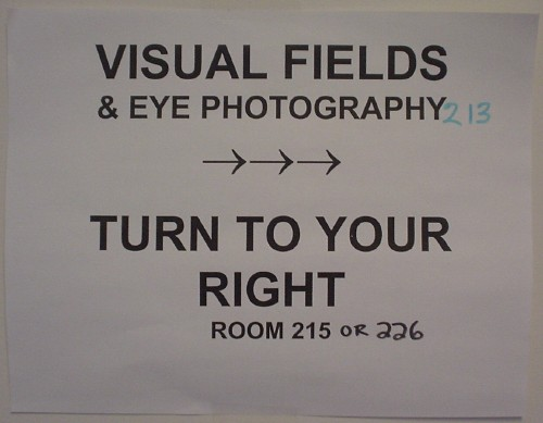 Laser-printed sheet with handwritten room-number corrections: 'Visual fields & eye photography →→→ Turn to your right'