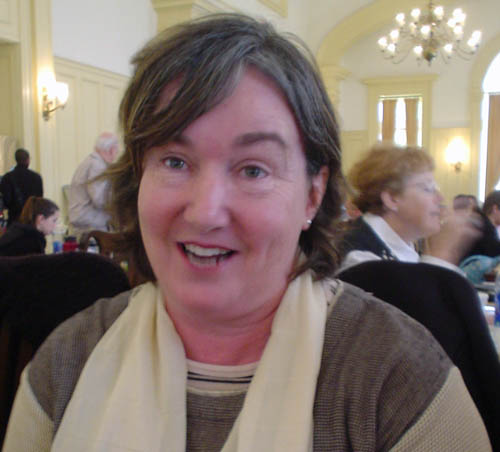 Smiling middle-aged woman with brown hair, brown sweater, cream scarf