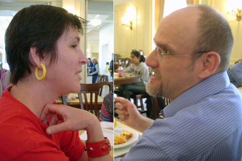 Two people in profile: Black-haired woman with yellow earrings and red shirt and bracelet facing right, balding brown-haired man with goatee and blue striped shirt facing left