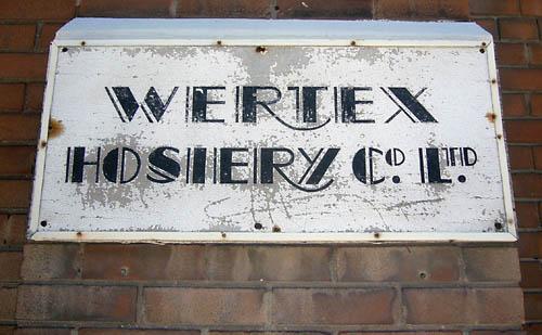 Weather-beaten wooden sign reads WERTEX HOSIERY Cº LTD in Art Deco type (with swash Rs)