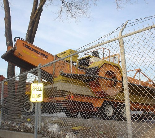 Giant orange woodchipper sits parked behind metal fence, in front of which stands a sunlit reflective sign reading SPEED BUMP