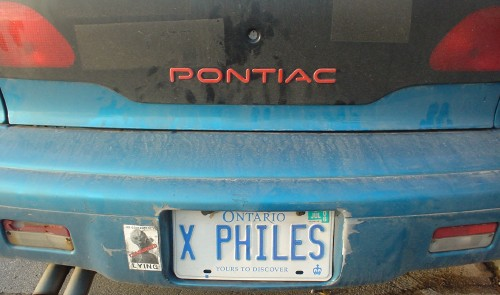 Blue Pontiac Sunbird's Ontario license plate reads X PHILES