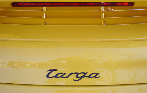 Script badge centred on yellow car below red taillight reads targa