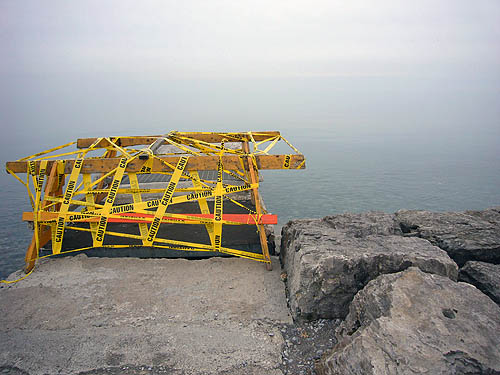 Void in an outcropping by waterside is festooned with sawhorses and yellow Caution tape