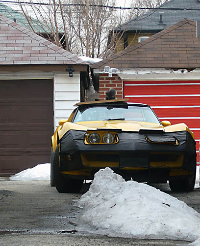 Yellow Corvette with black bra over front end parked between two houses