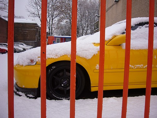 Yellow Honda sits under a blanket of snow behind a red fence