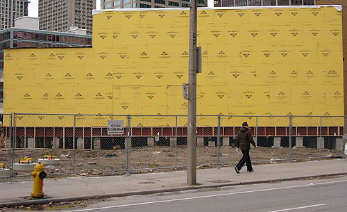 Person on sidewalk walks past L-shaped wall covered in yellow Tyvek panels with black labelling