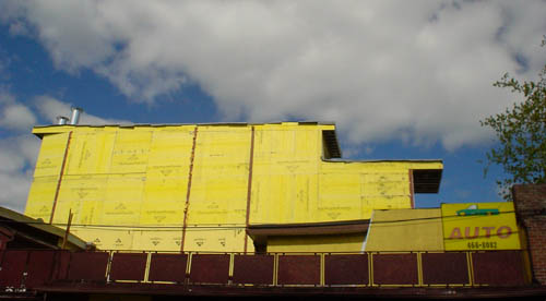 Two-storey extension of building has the shape of a locomotive and is finished in bright-yellow Tyvek against a cloudy blue sky