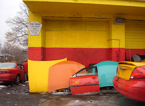 Yellow-and-red garage, with yellow-and red taxis parked nearby and yellow, orange, red, and aquamarine car hoods, trunks, and doors leaning against the wall