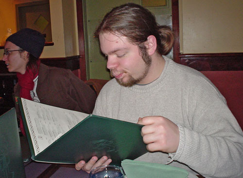 Woman in cap looks to the side as young man with beard and long hair peruses a menu