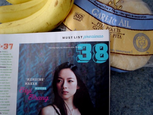 A bag of garlic pitas, bananas, and a corner of a magazine page showing a photo of Ziyi Zhang, with a script font whose crossed Zs are hard to discern