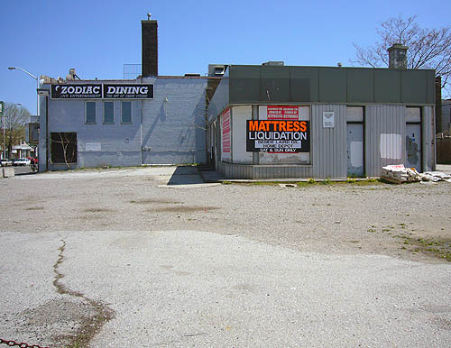 Desolate concrete lot holds buildings with signs reading ZODIAC DINING and MATTRESS LIQUIDATION SAT & SUN ONLY