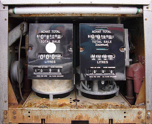 Innards of rusted gas pump show old mechanical ACHAT TOTAL and LITRES displays