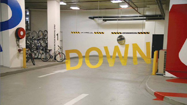 Yellow letters read DOWN on parking-garage wall when viewed from the correct angle