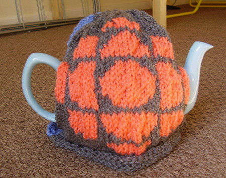 Tea cozy has knit pattern of the CBC exploding pizza