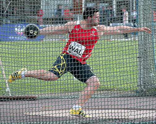 Brett Morse winding up to throw the discus, seen through a fence