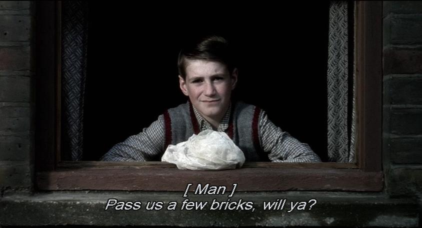 Boy sits gazing out a window. MAN: Pass us a few bricks, will ya?