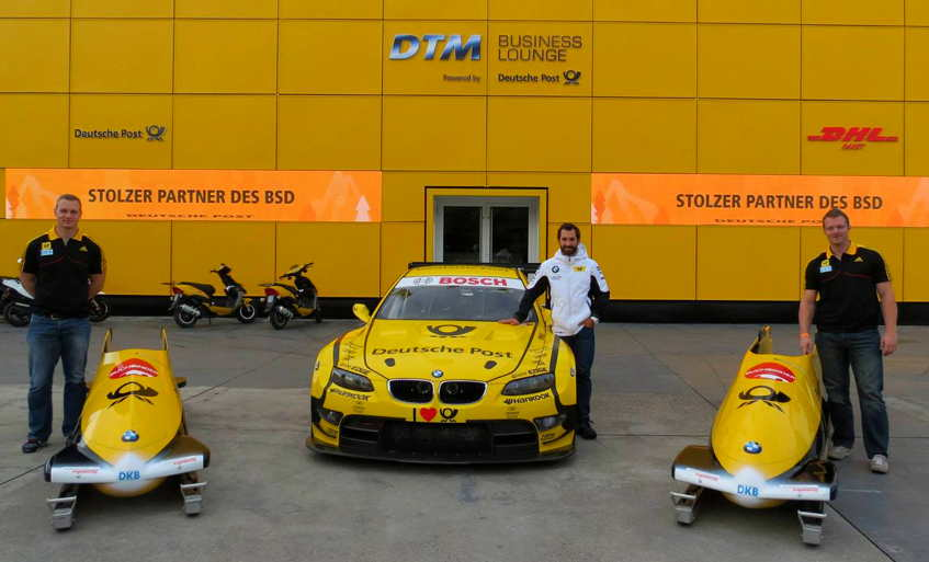 Two yellow bobsleds, a yellow race BMW, a yellow enamel-panel building, two bobsledders and a driver