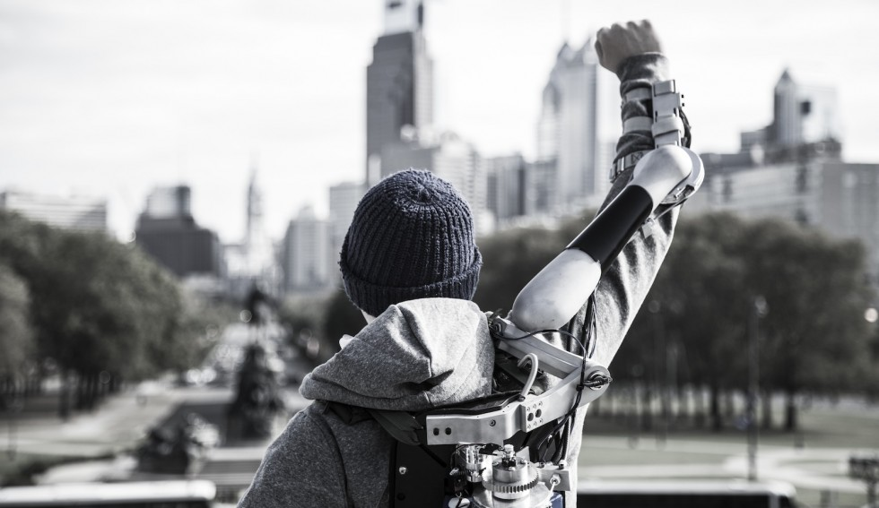 Seen from behind, a teenage boy raises his right arm in a fist. Hydraulics and an armature sit on top of his arm and connect to a mechanical backpack