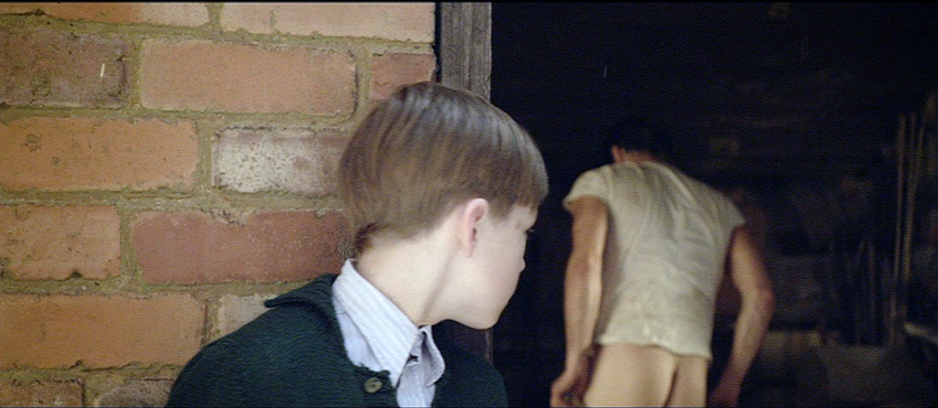 Boy looks back at workman pulling off his trousers in barn