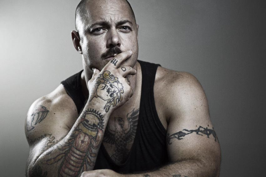 Sepiatone photograph of well-muscled man in tank top (with tattoos all the way down right arm onto right hand)